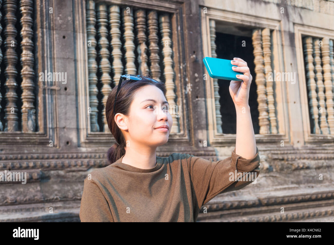 Female traveler selfie with her smartphone in angkor wat siem reap cambodia - Stock Image