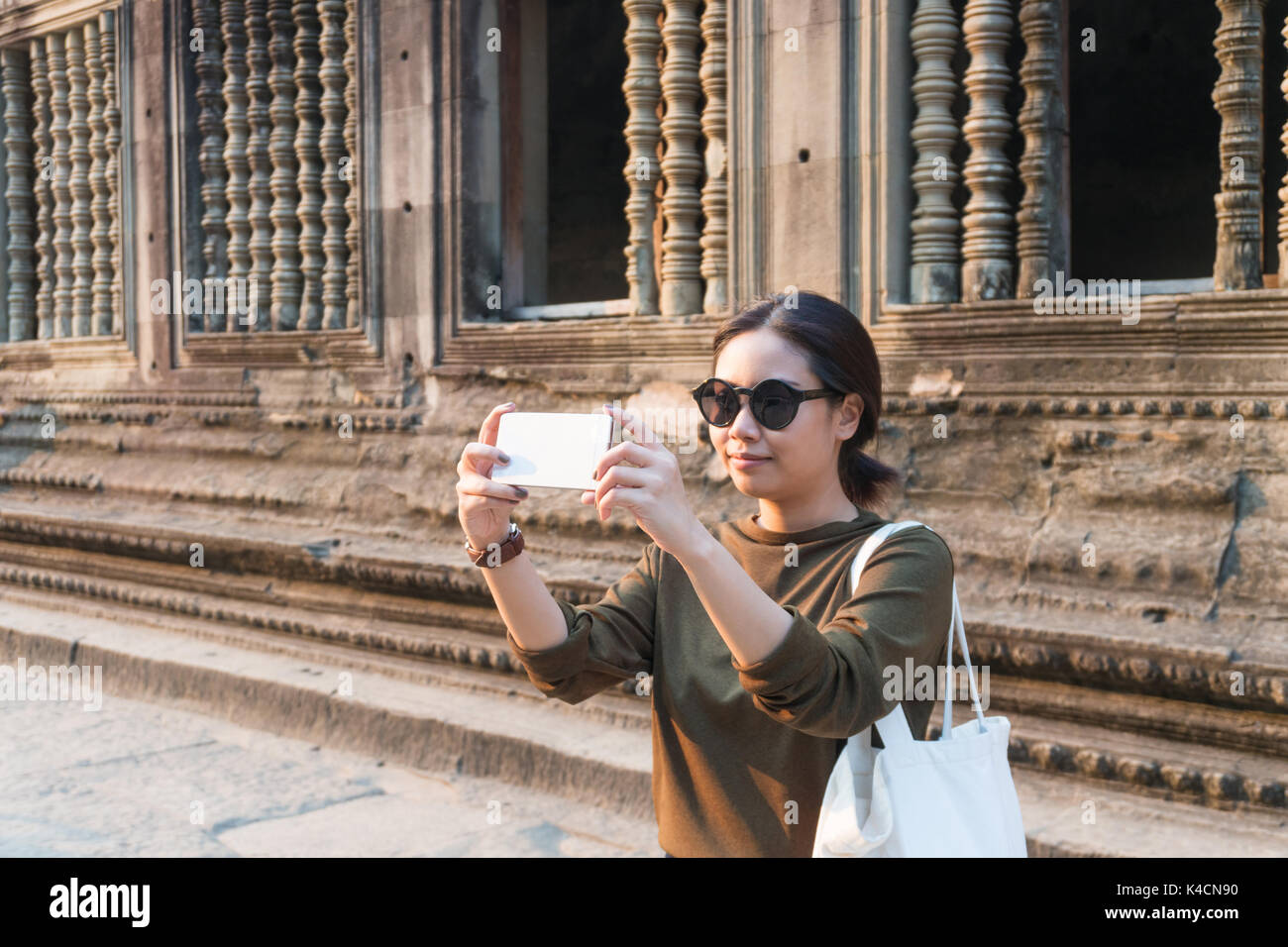 Female traveler taking photo with her smartphone in angkor wat siem reap cambodia - Stock Image