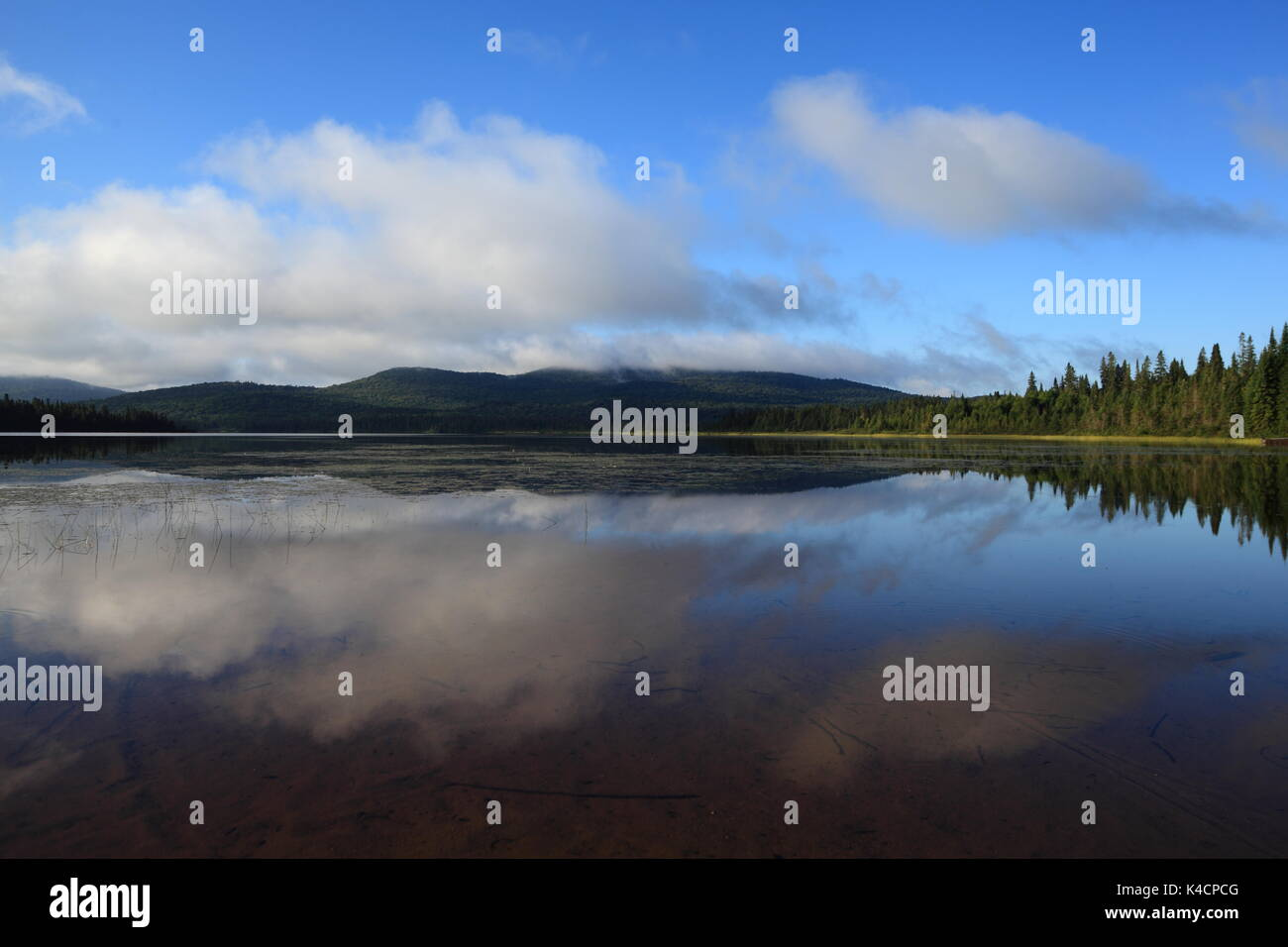 The morning clouds are sitting on the Laurentides Hills at Lac Escalier in Mont-Tremblant National Park, Quebec, Canada, August 13, 2017 - Stock Image