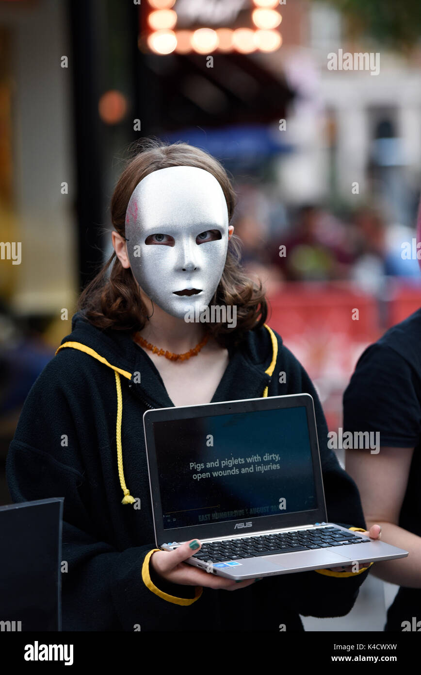 Earthlings Experience animal rights activists protesting outside Burger King in Leicester Square, London. Protester wearing anonymous mask - Stock Image