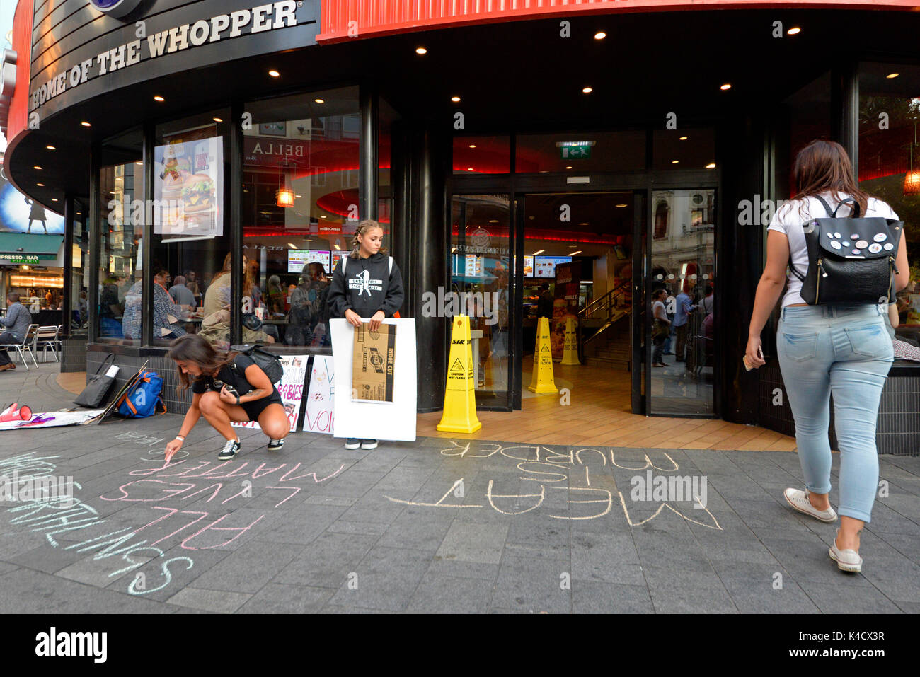 Animal rights activists protesting outside Burger King in Leicester Square, London. Chalking slogans on pavement - Stock Image
