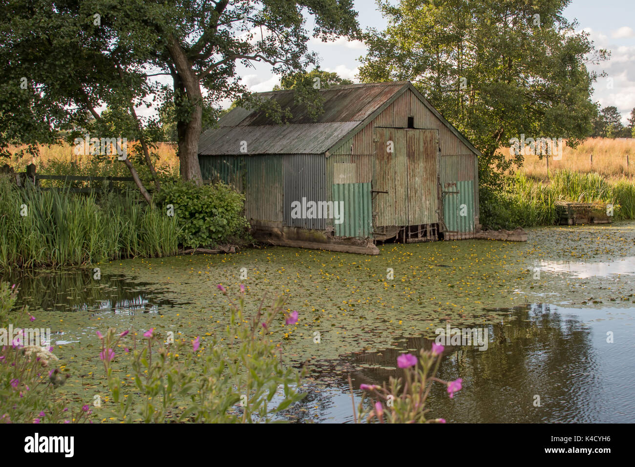 An old metal corrugated derelict boat shed a standing in the corner of a pool showing signs of neglect - Stock Image