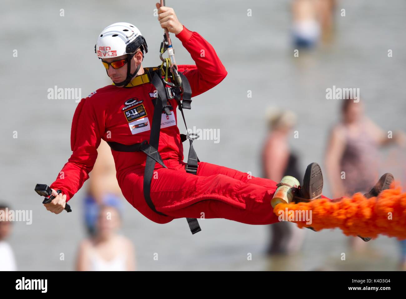 A member of the Red Devils Parachute Team having fun on the Bournemouth Zip Wire - Stock Image