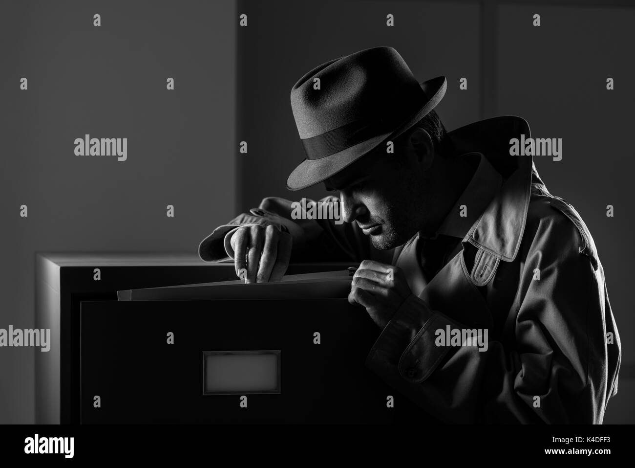 Vintage undercover criminal spy stealing files in a filing cabinet late at night, security and data theft concept - Stock Image