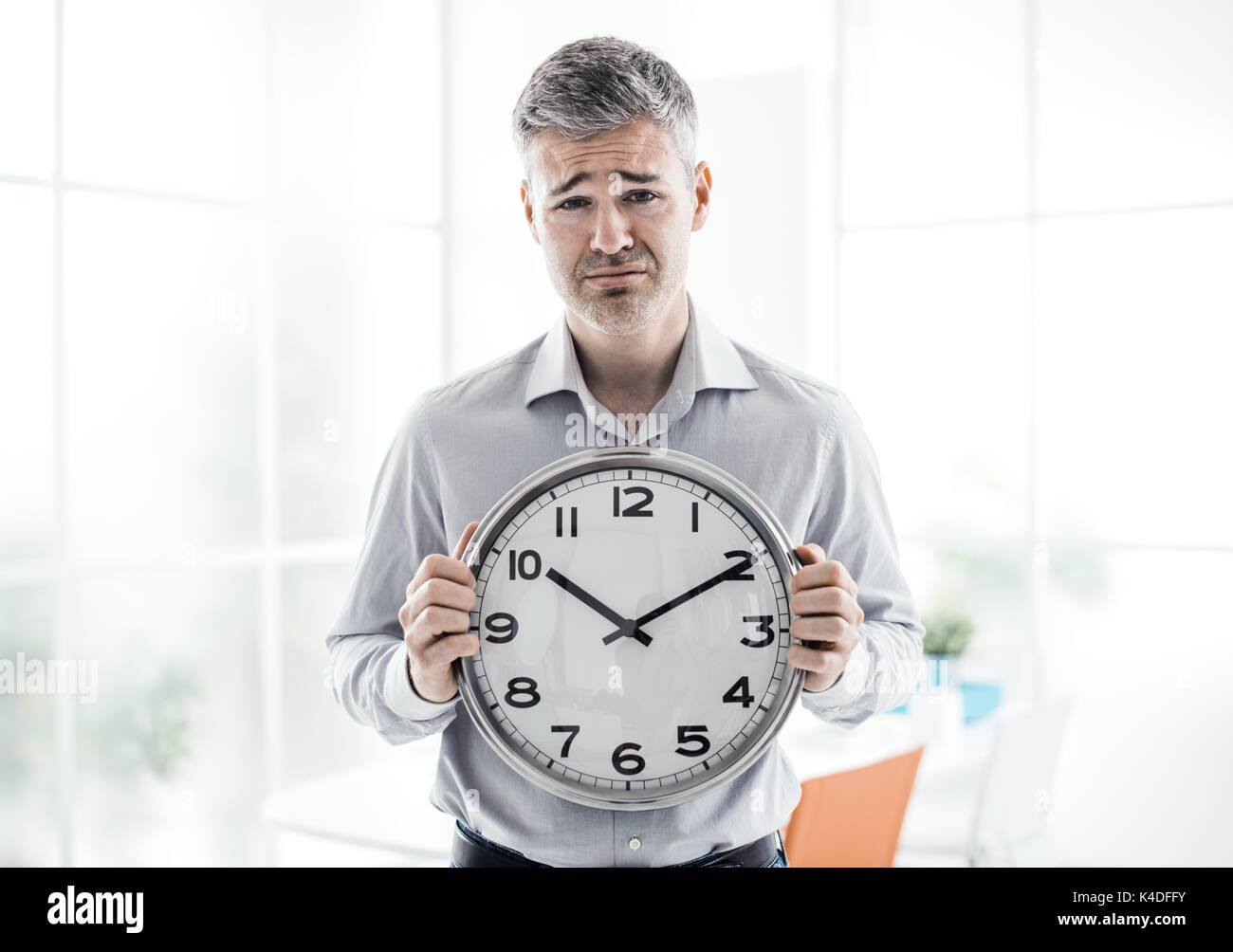 Business, time management and deadlines: sad businessman holding a clock, he is missing a deadline - Stock Image