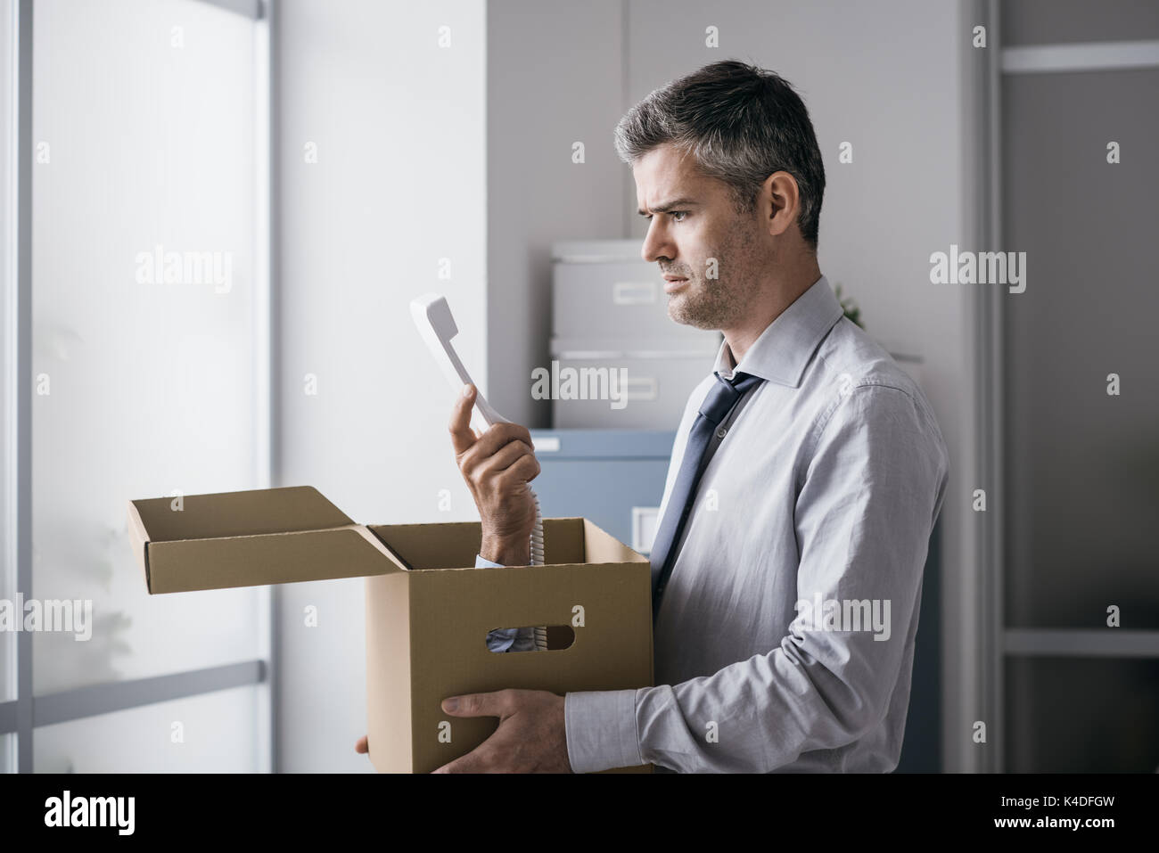 Shocked office worker receiving a surprise call inside a cardboard box, stressful job and stalking concept - Stock Image
