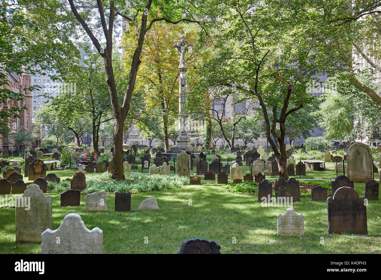Trinity Church cemetery with green grass in a sunny day. This is the only active cemetery in Manhattan. - Stock Image
