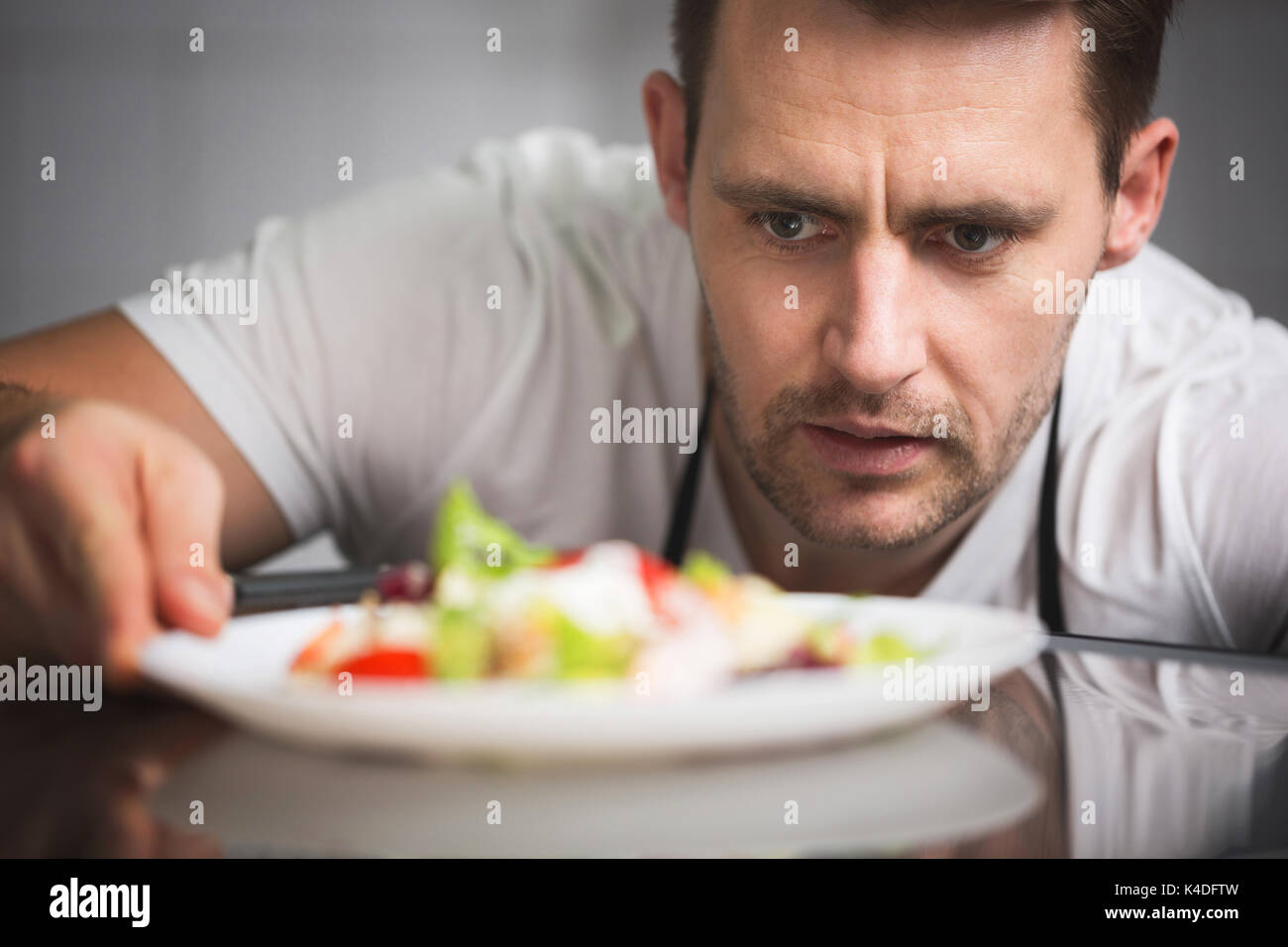 Close up front portrait of male chef preparing salad - Stock Image