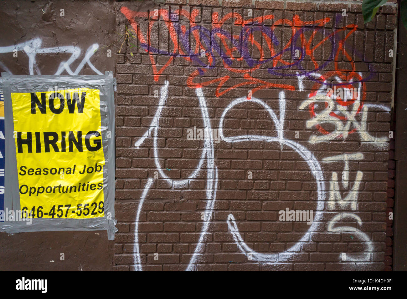 Hiring sign amidst graffiti under the elevated train along Jerome Avenue in the Bronx borough of New York is seen on Sunday, September 3, 2017.  (© Richard B. Levine) - Stock Image