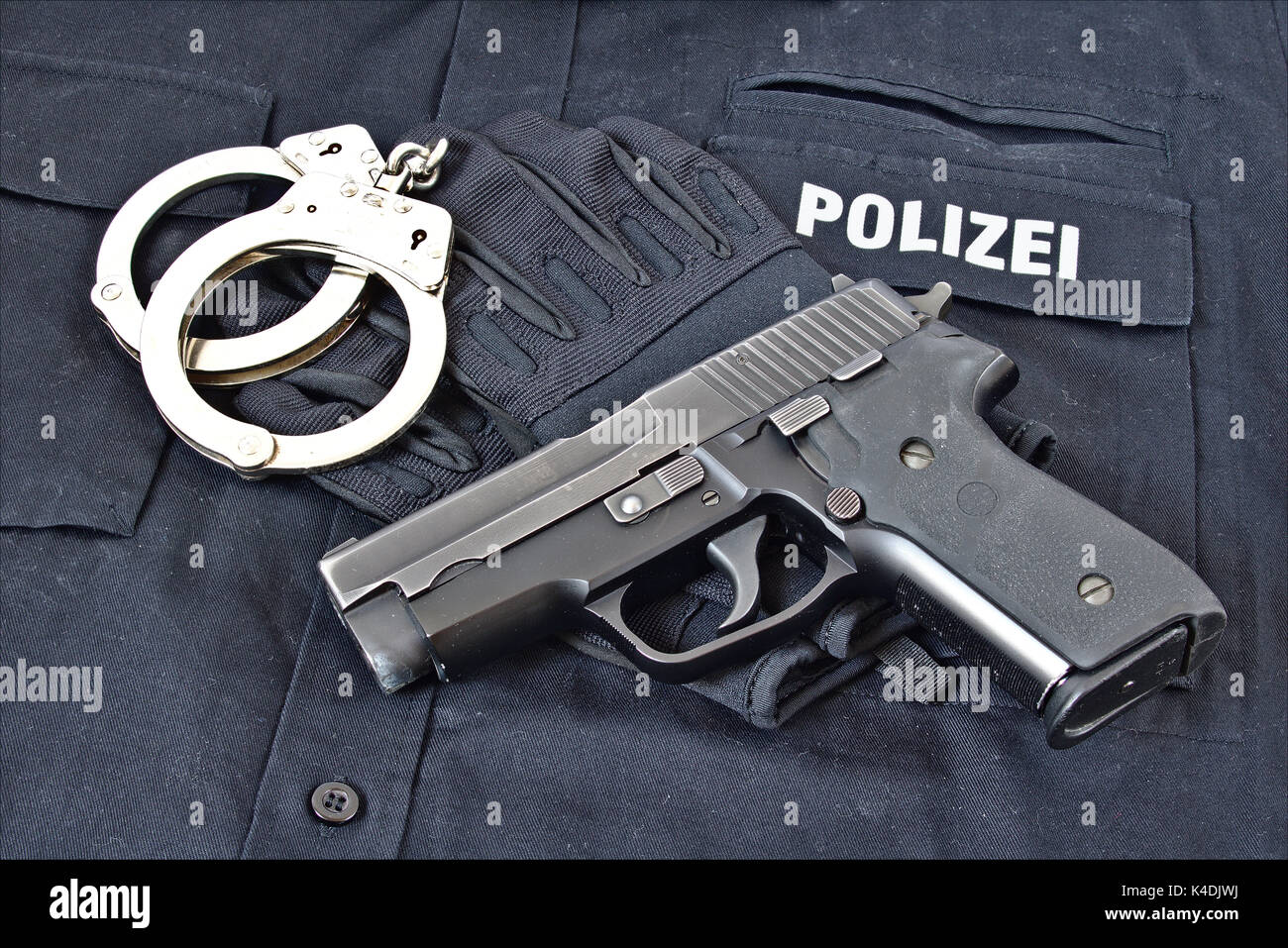 Handgun with handcuffs and gloves on blue uniform shirt with 'Police' in German on it - Stock Image