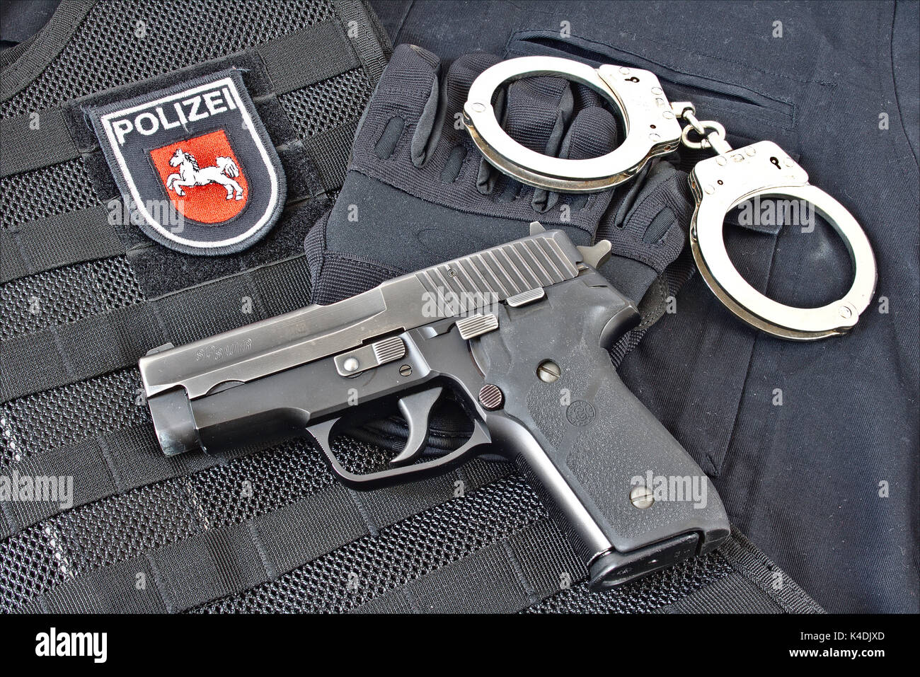 Handgun with handcuff, gloves on blue uniform shirt and tactical vest with patch of Niedersachsen State Police, Germany - Stock Image