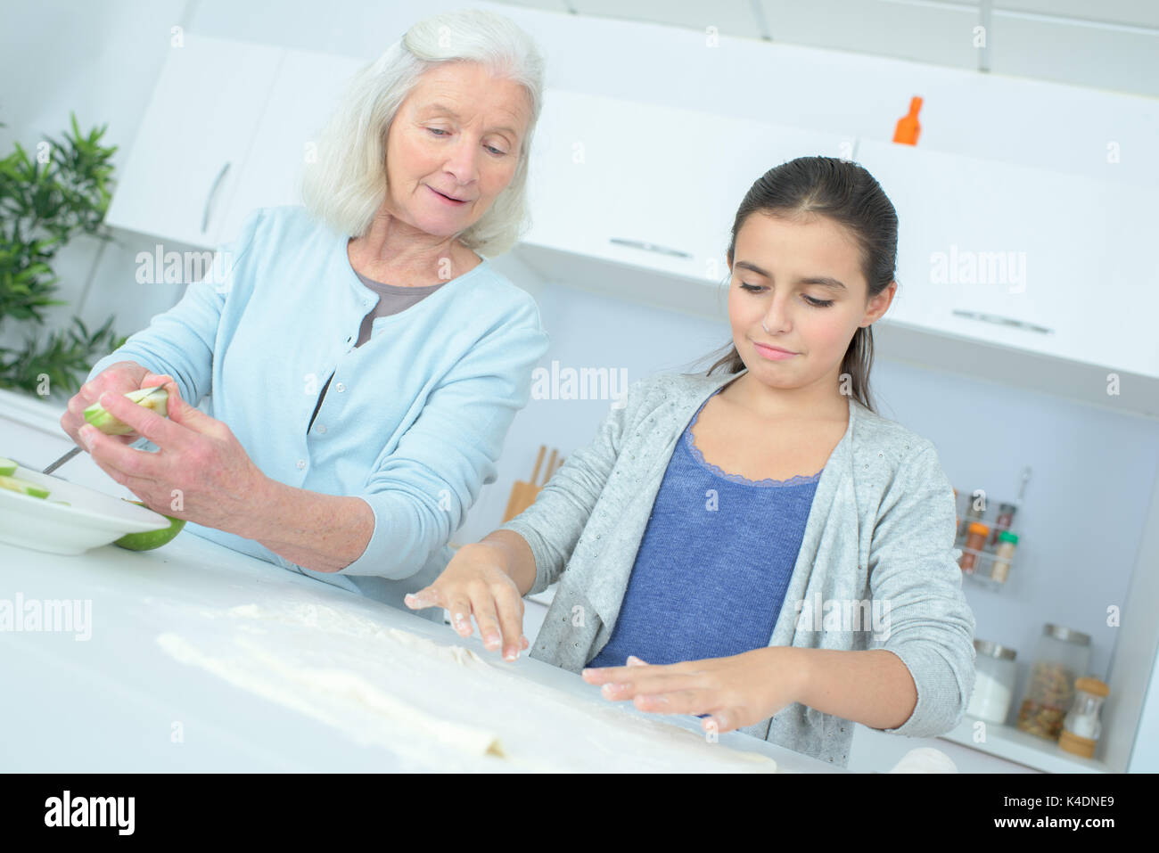 senior nanny cooking with child - Stock Image