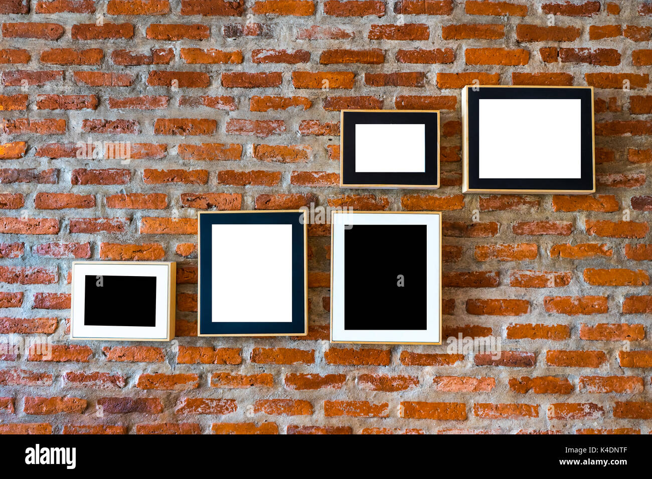 Brick wall decorated with photo frames left blank in black and white - Stock Image