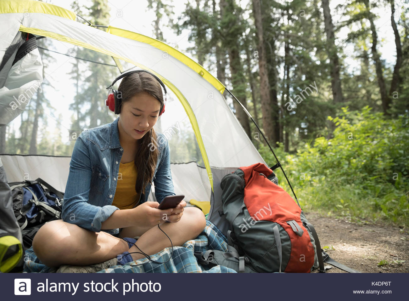 Teenage girl relaxing, camping and listening to music with headphones and mp3 player in tent - Stock Image