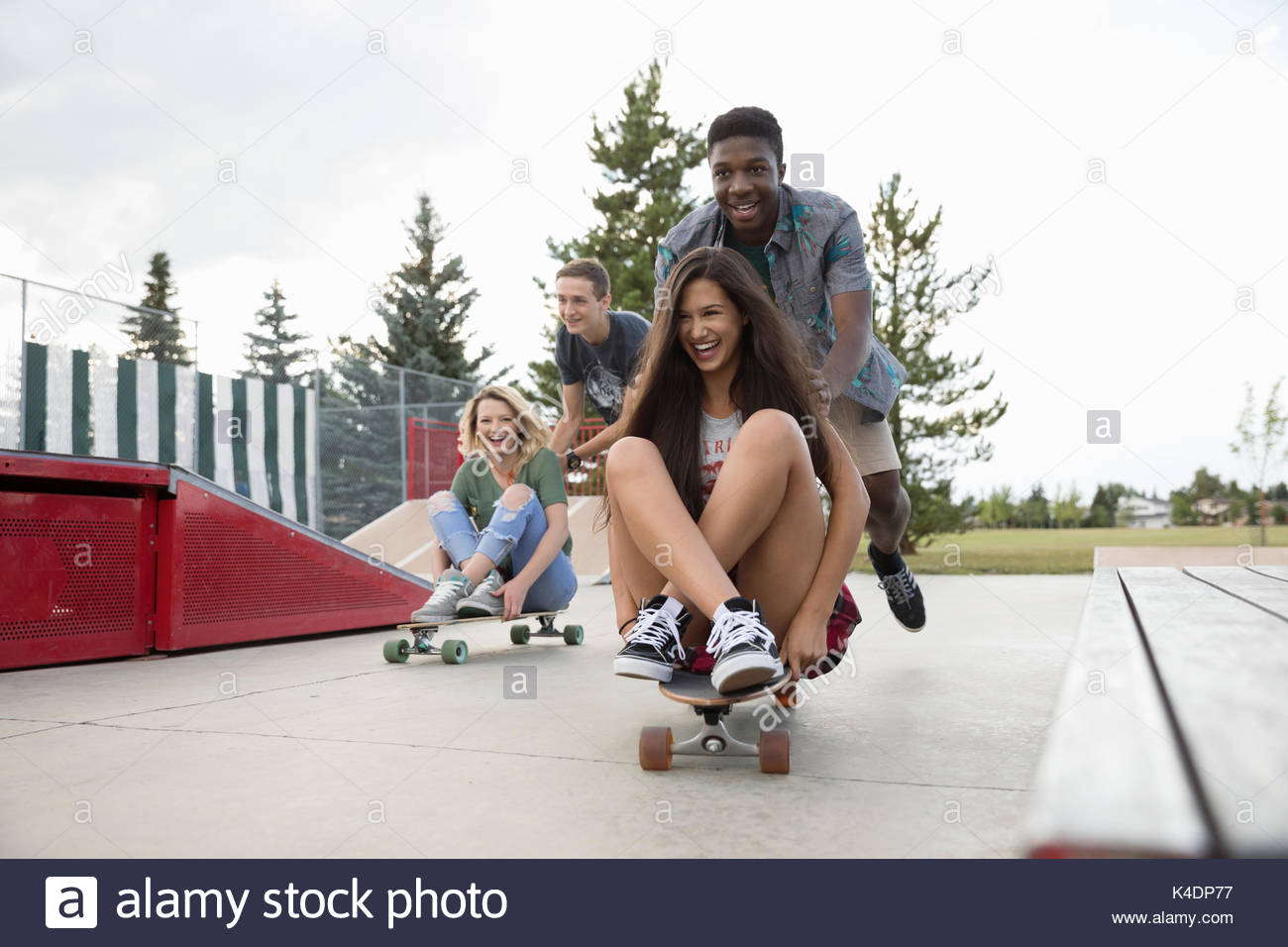 Playful teenage friends playing, pushing skateboards at skate park - Stock Image