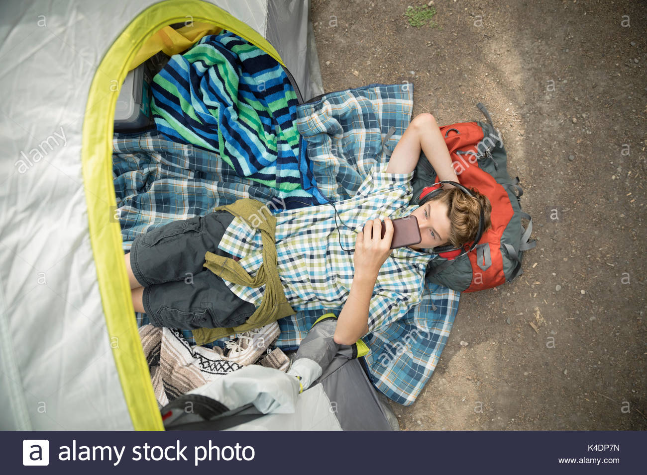 Overhead view teenage boy relaxing, camping and listening to music with headphones and mp3 player in tent - Stock Image