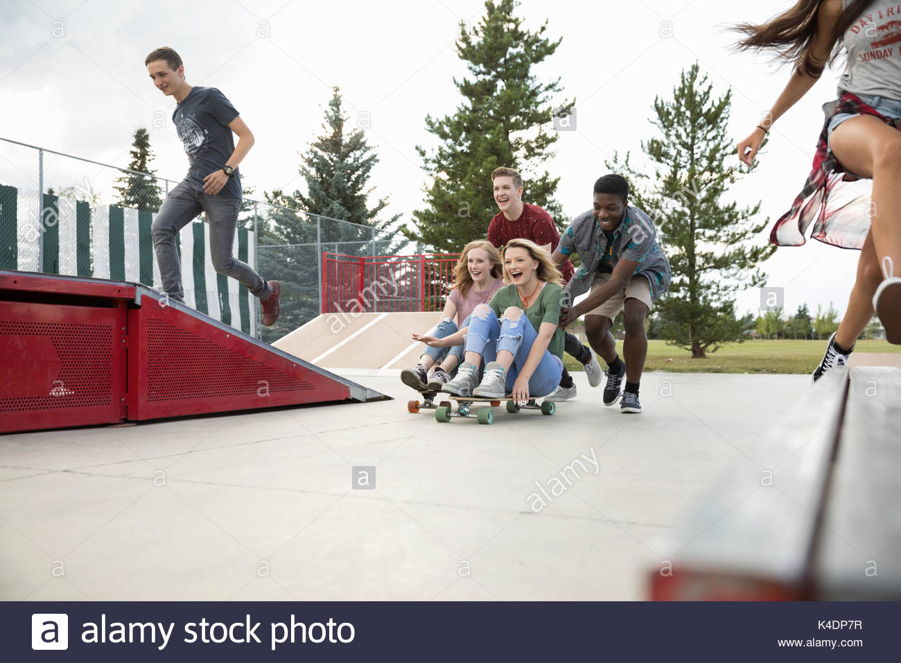 Playful teenage friends playing, pushing skateboards in skate park - Stock Image