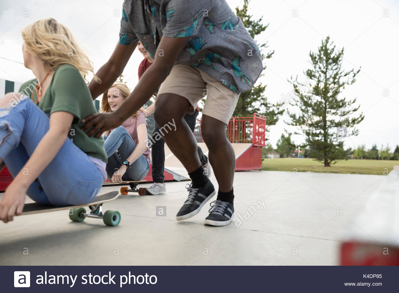 Teenage friends playing, pushing skateboards in skate park - Stock Image