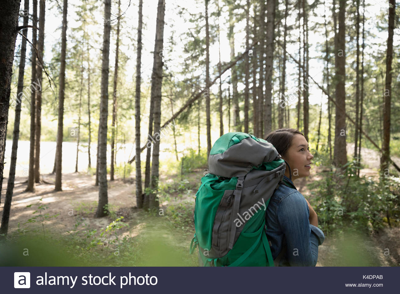 Curious teenage girl with backpack hiking in woods - Stock Image