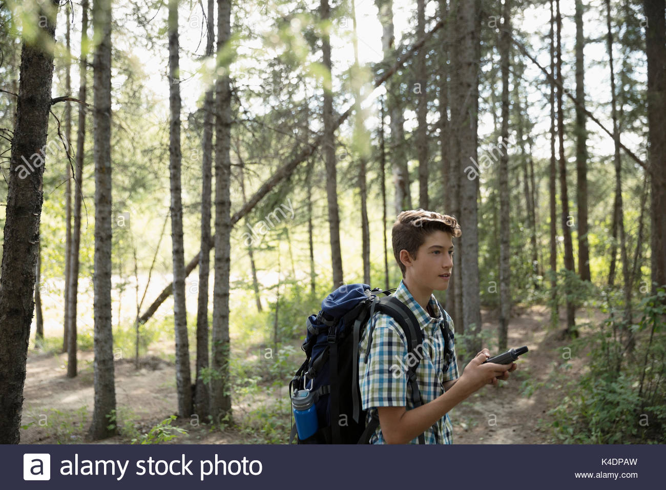 Teenage boy with backpack using compass, hiking in woods - Stock Image