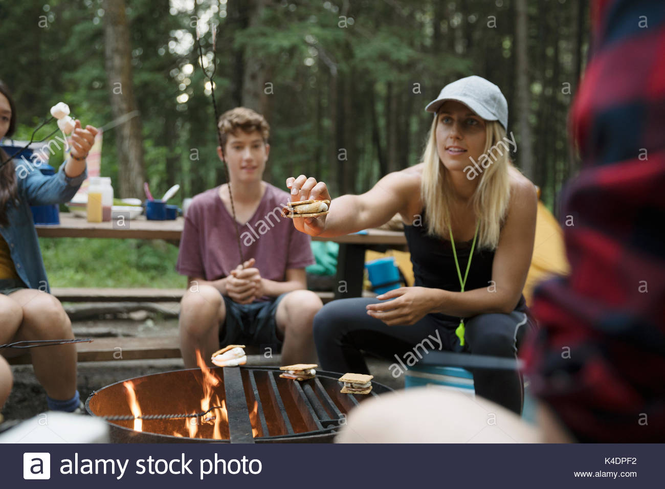Female teacher and teenage outdoor school students making smores at campsite campfire - Stock Image