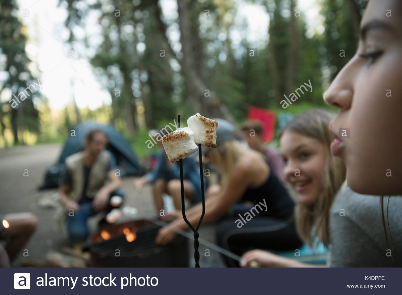 Teenage girl outdoor school students blowing on toasted marshmallow at campsite campfire - Stock Image