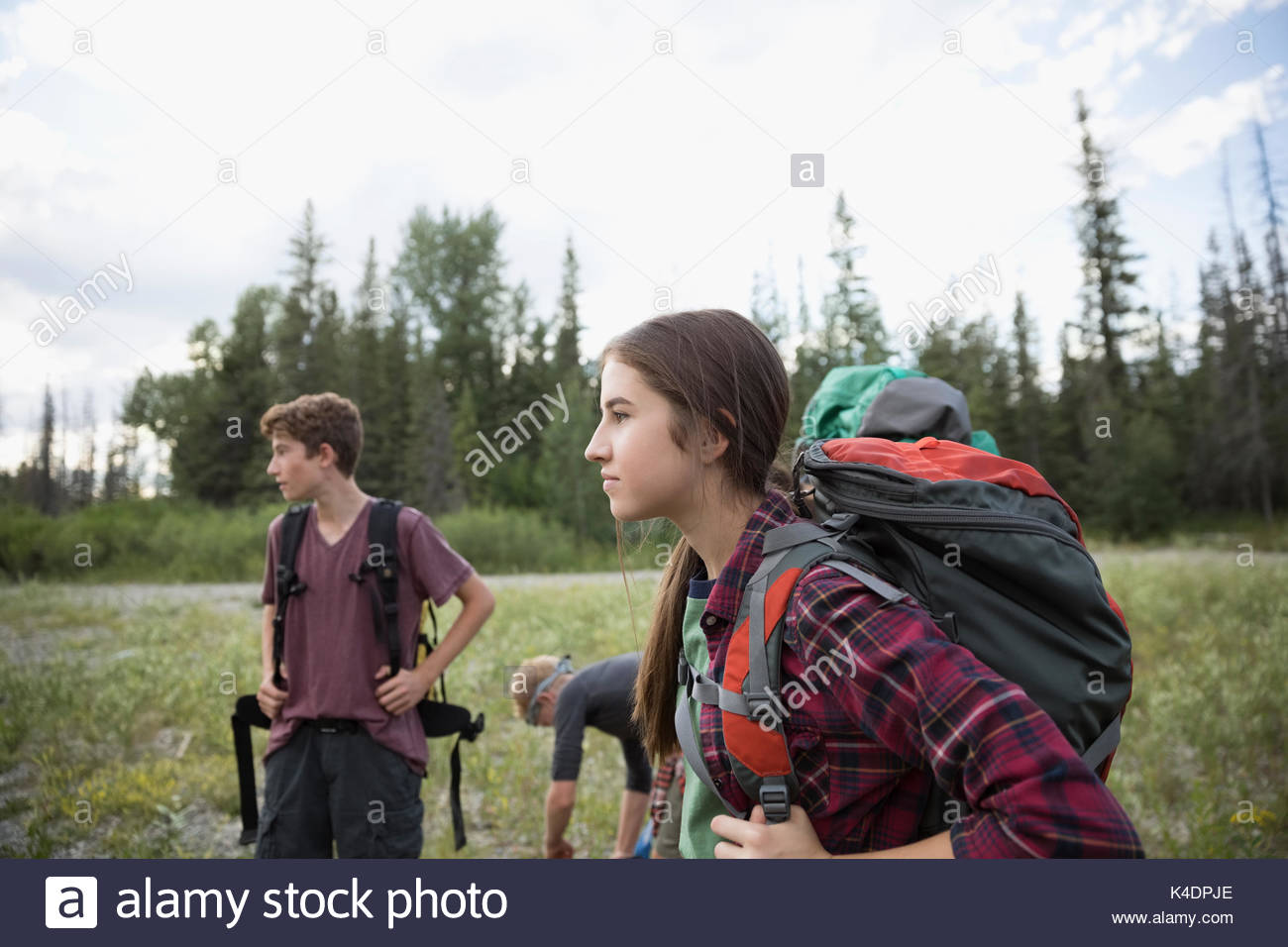 Teenage outdoor school students with backpacks hiking in woods - Stock Image
