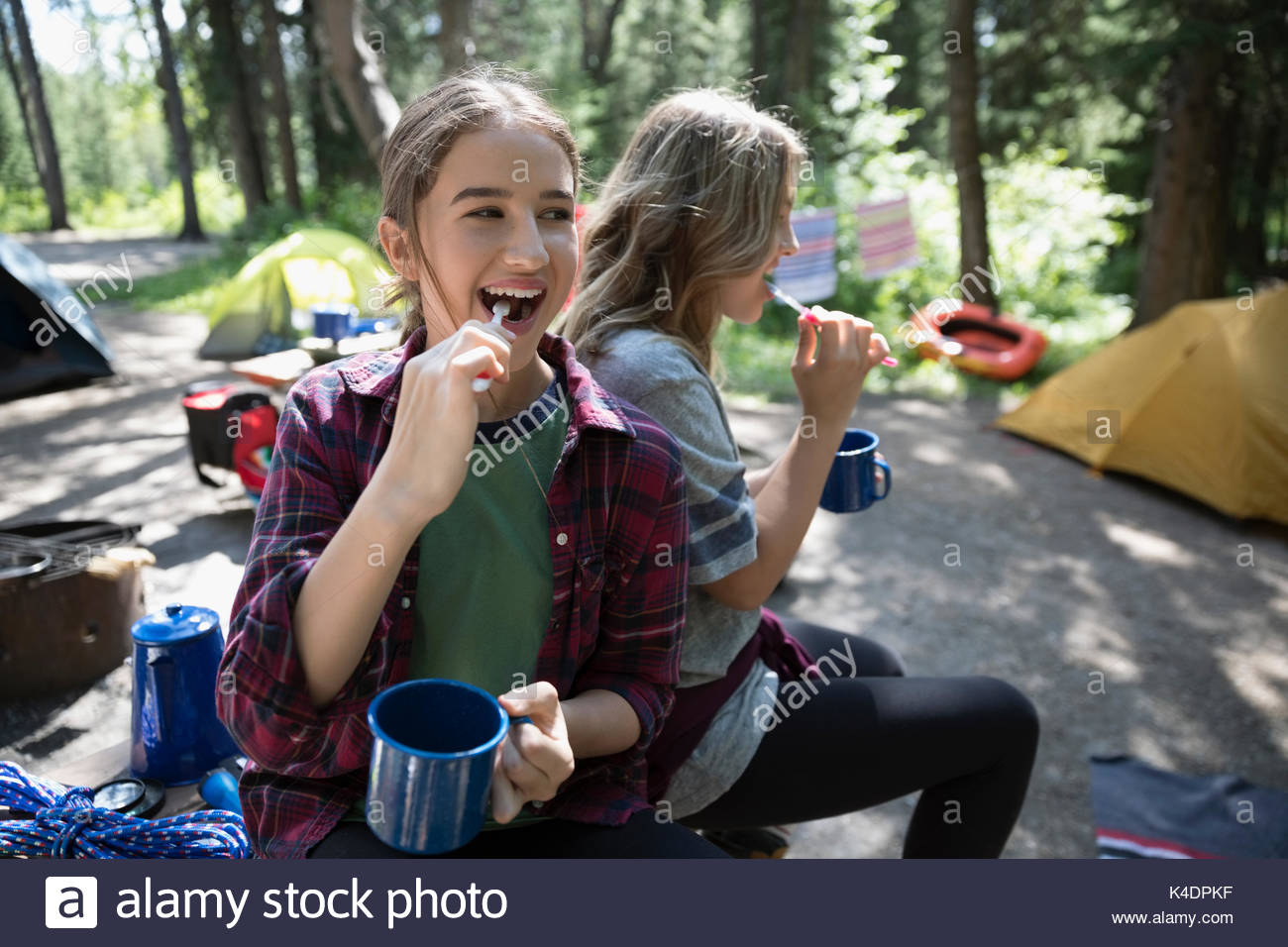 Smiling teenage girl friends brushing teeth with toothbrushes and mugs at outdoor school campsite - Stock Image