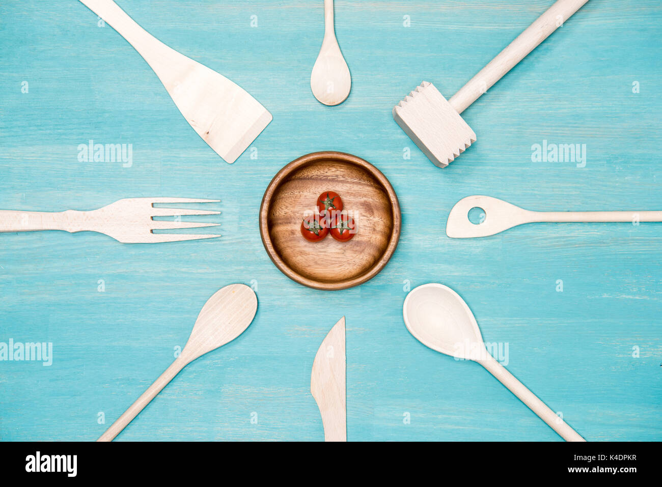 top view of wooden cooking utensils with cherry tomatoes on plate Stock Photo