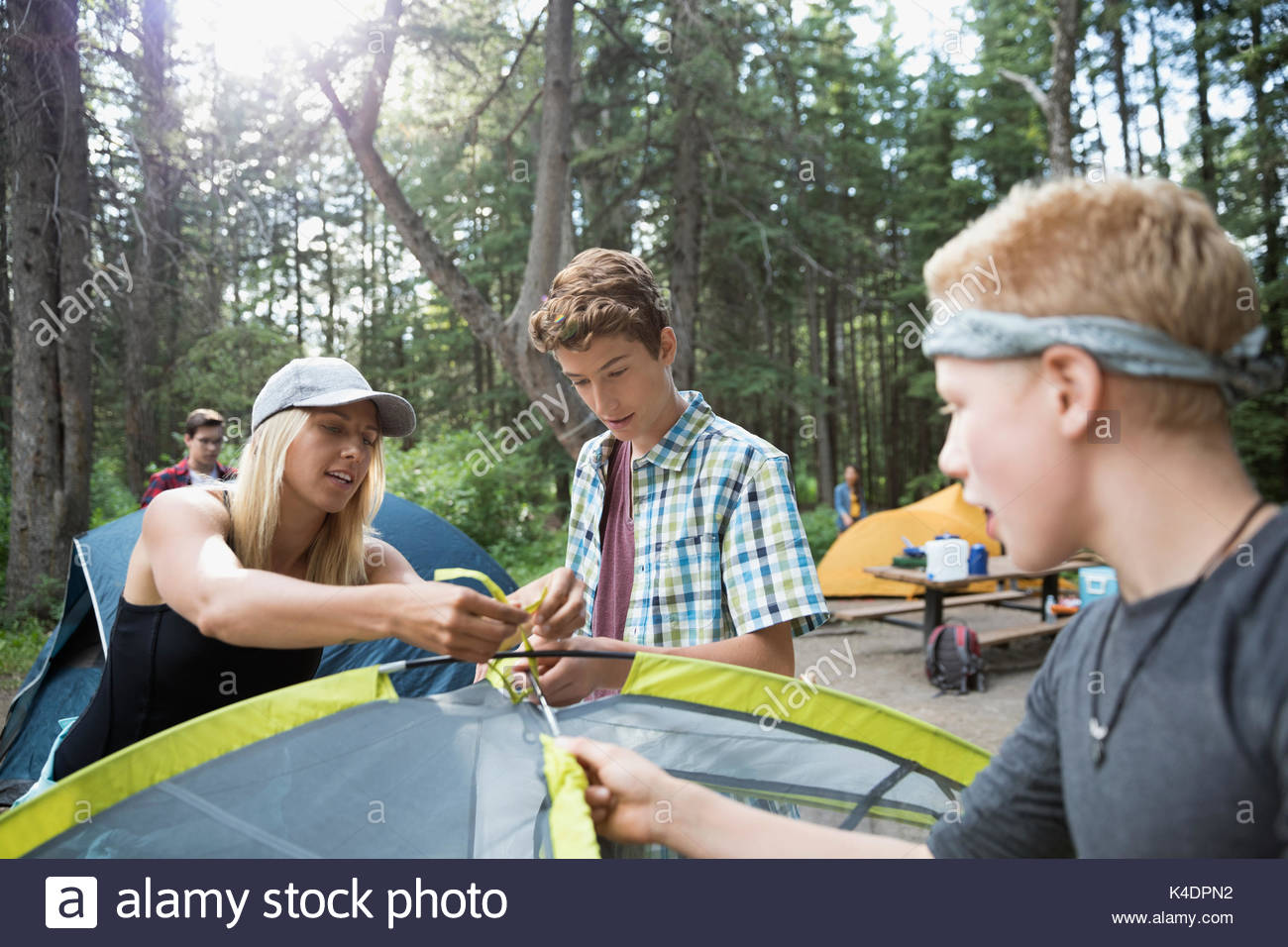 Female teacher showing teenage outdoor school boy students how to pitch a tent at campsite - Stock Image