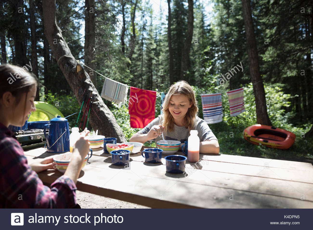 Teenage girl friends eating breakfast at sunny outdoor school campsite picnic table - Stock Image