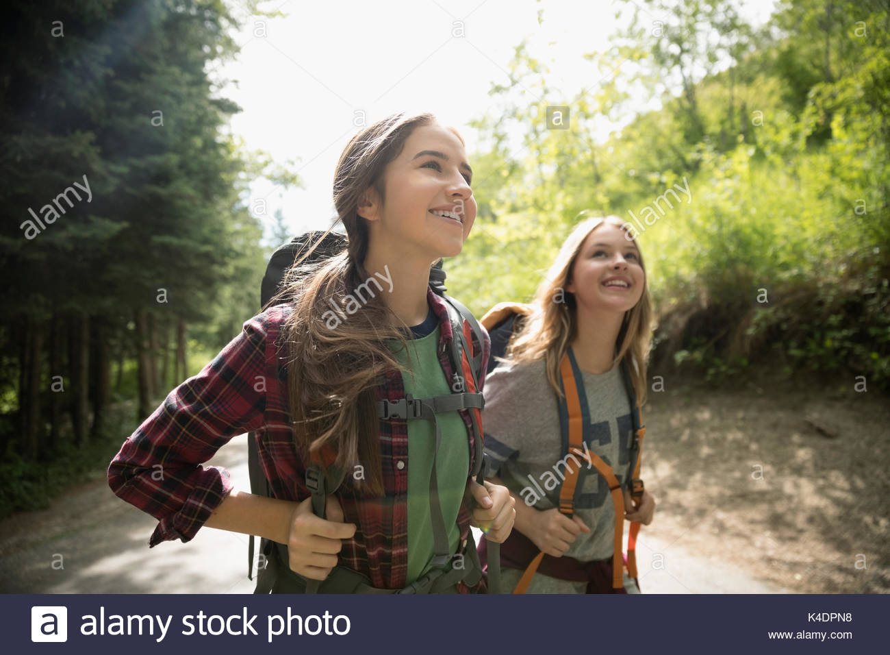 Curious, smiling teenage girl friends with backpacks hiking in woods - Stock Image