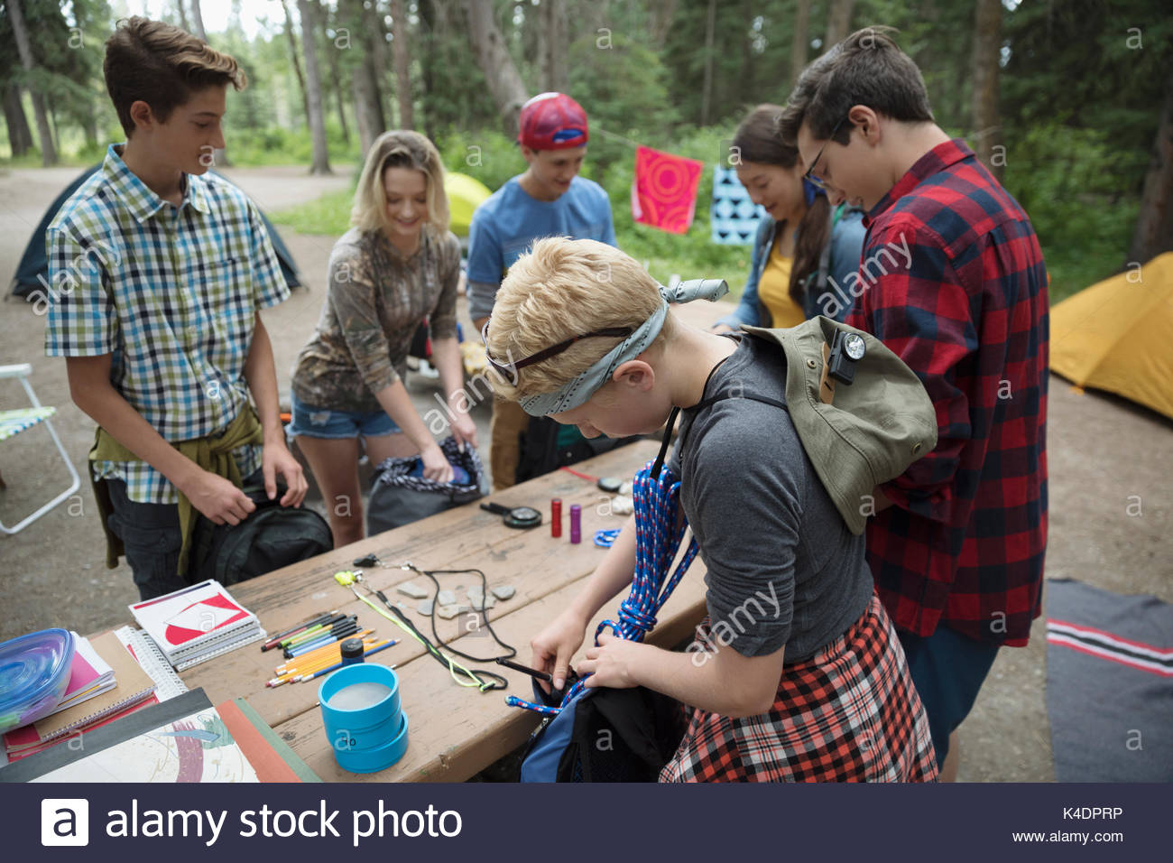 Students packing equipment in backpacks at outdoor school campsite picnic table - Stock Image