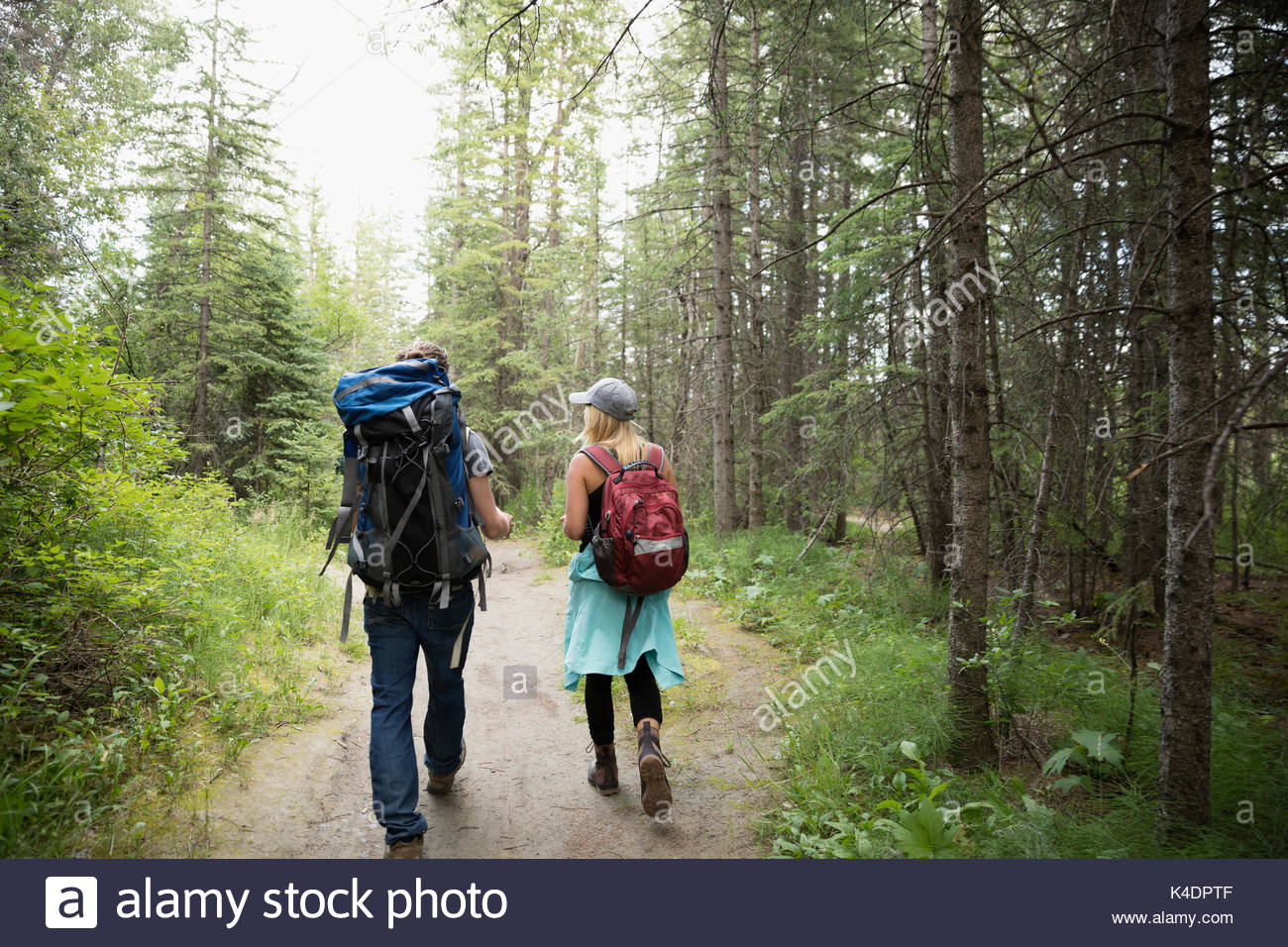 Couple with backpacks backpacking, hiking on trail in woods among trees - Stock Image