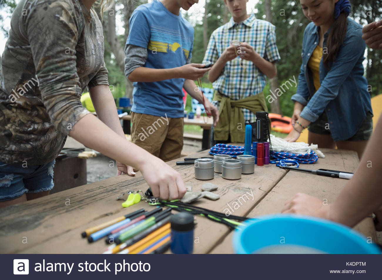 Teenage students preparing equipment at outdoor school campsite picnic table - Stock Image