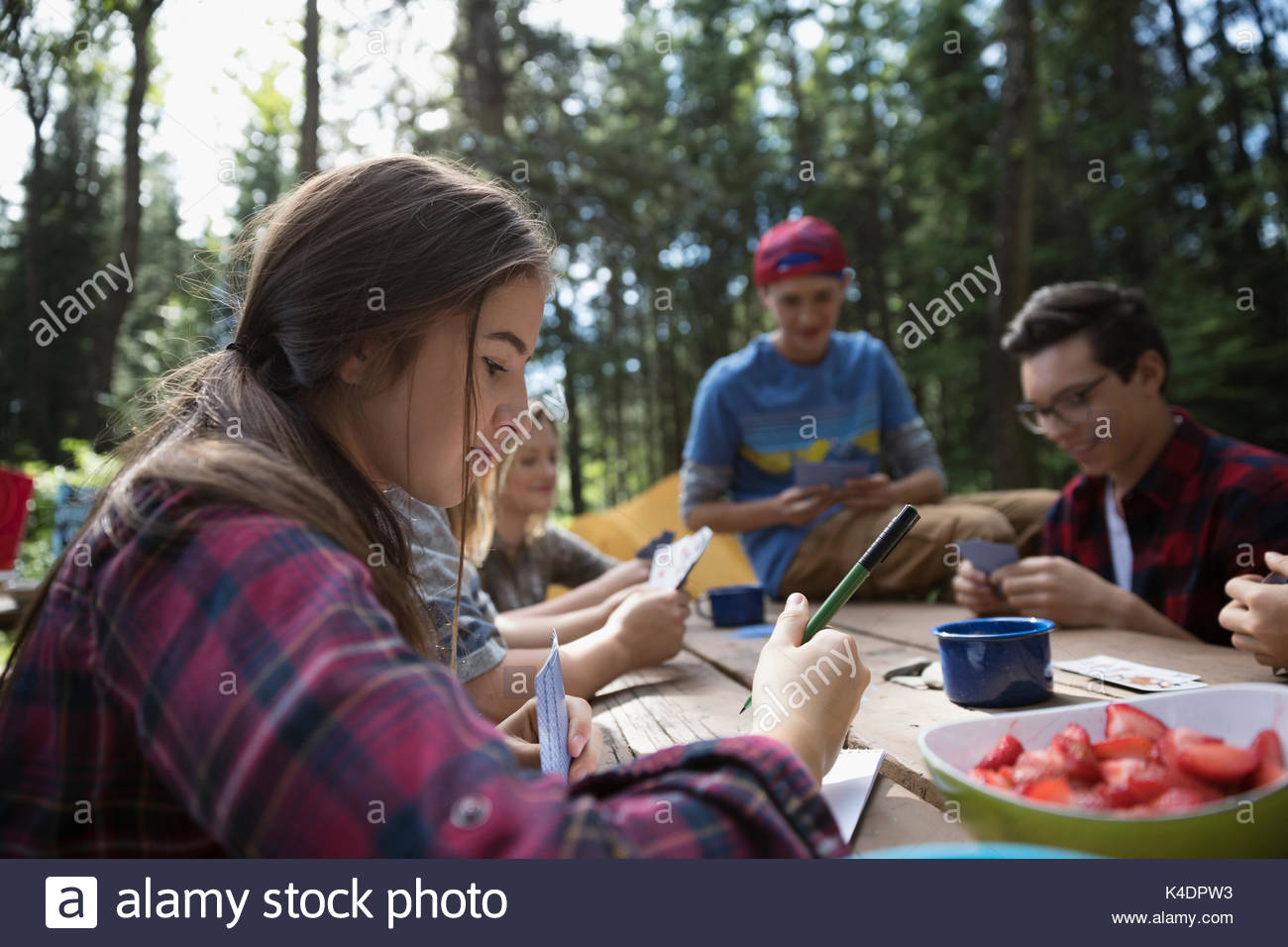Teenage outdoor school girl student writing at campsite picnic table - Stock Image