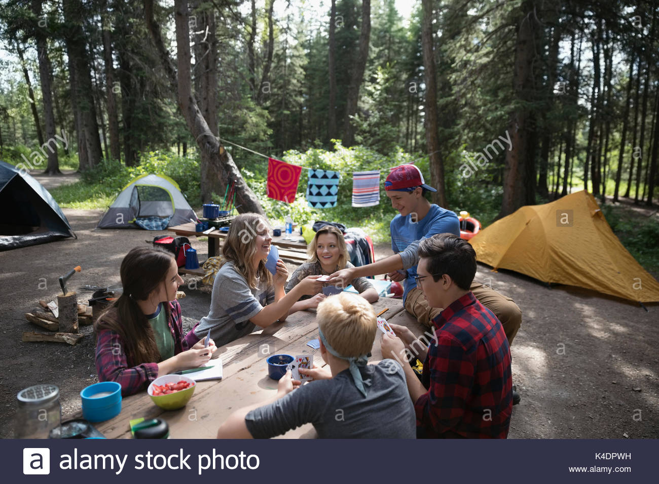 Teenage outdoor students at campsite picnic table - Stock Image