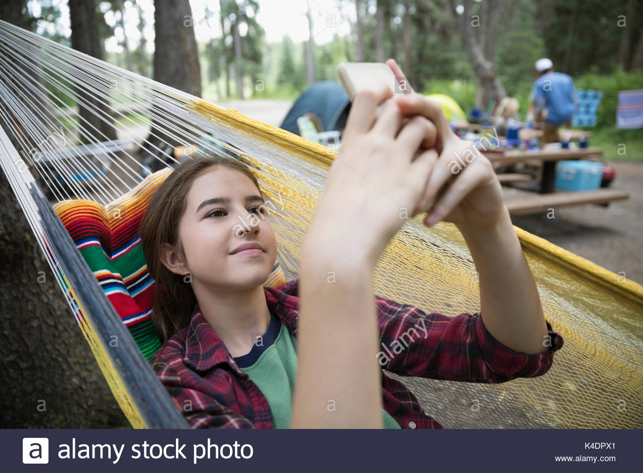 Teenage girl relaxing, texting with cell phone in hammock at outdoor school campsite - Stock Image