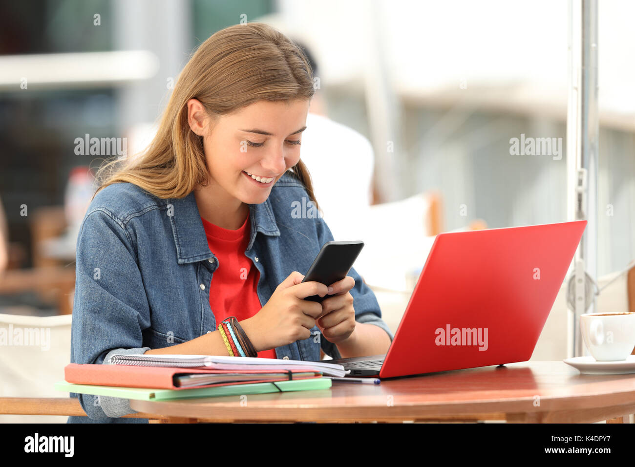 Cheerful student texting on a mobile phone sitting in a bar terrace - Stock Image