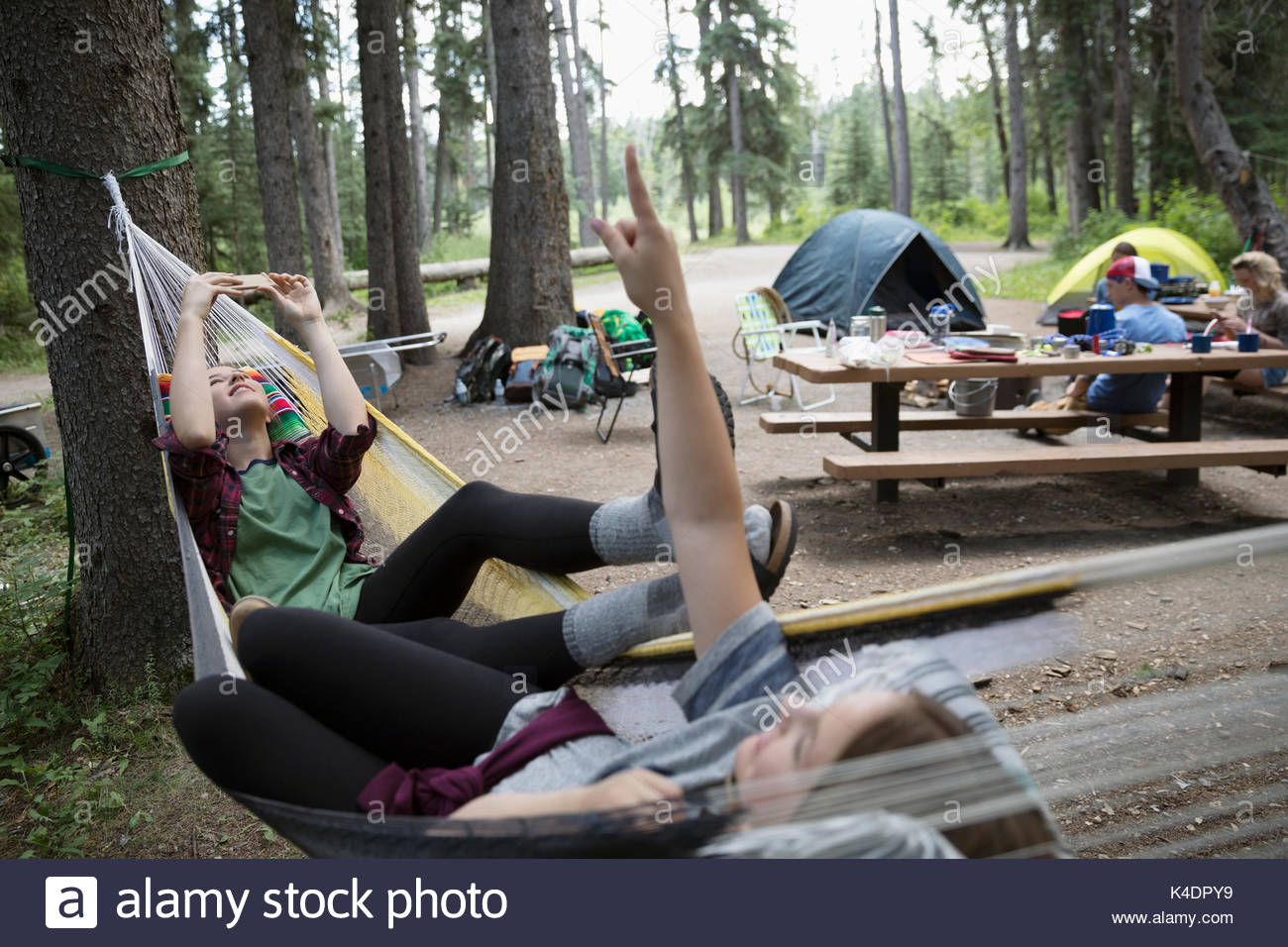 Teenage girl friends relaxing, laying in hammocks at outdoor school campsite - Stock Image