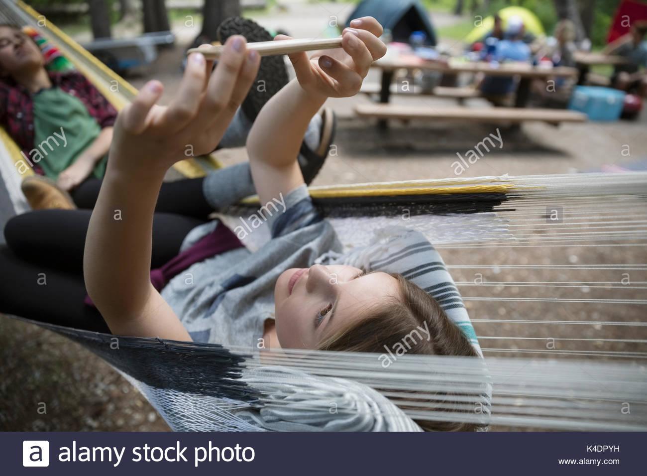 Teenage girl with camera phone taking selfie  in hammock at outdoor school campsite - Stock Image