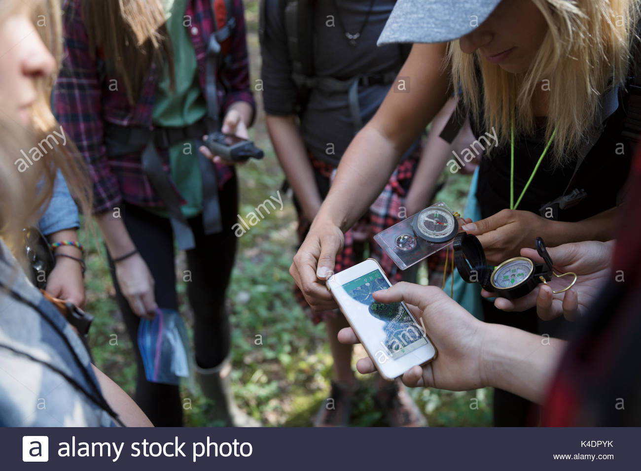 Female teacher and teenage outdoor school students using compass and smart phone gps, hiking - Stock Image