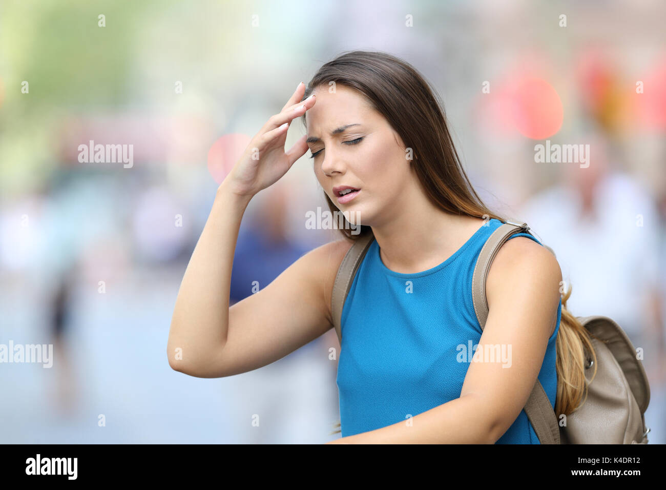Single woman suffering headache outdoors in the street - Stock Image