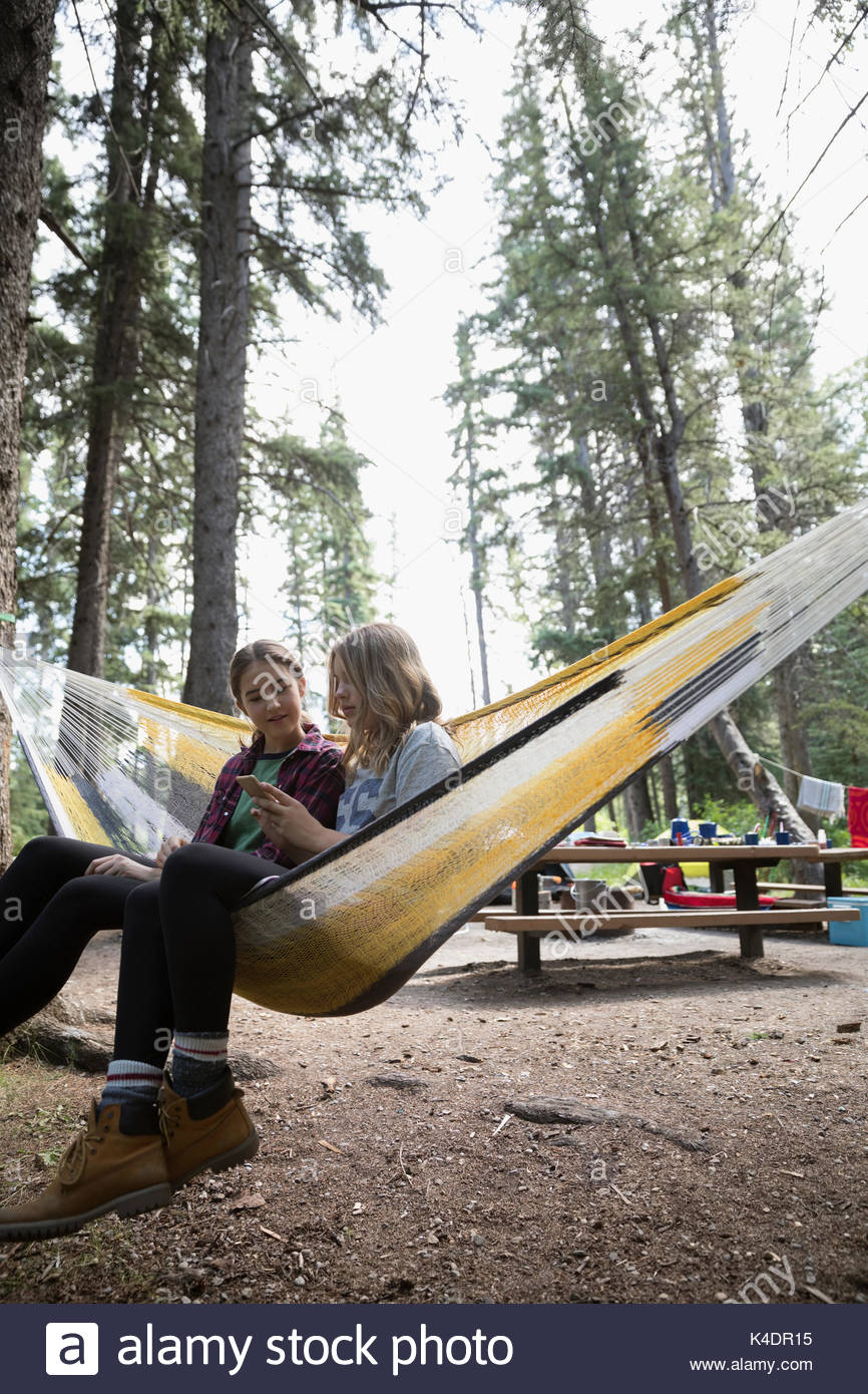 Teenage girl friends texting with cell phone in hammock at outdoor school campsite - Stock Image