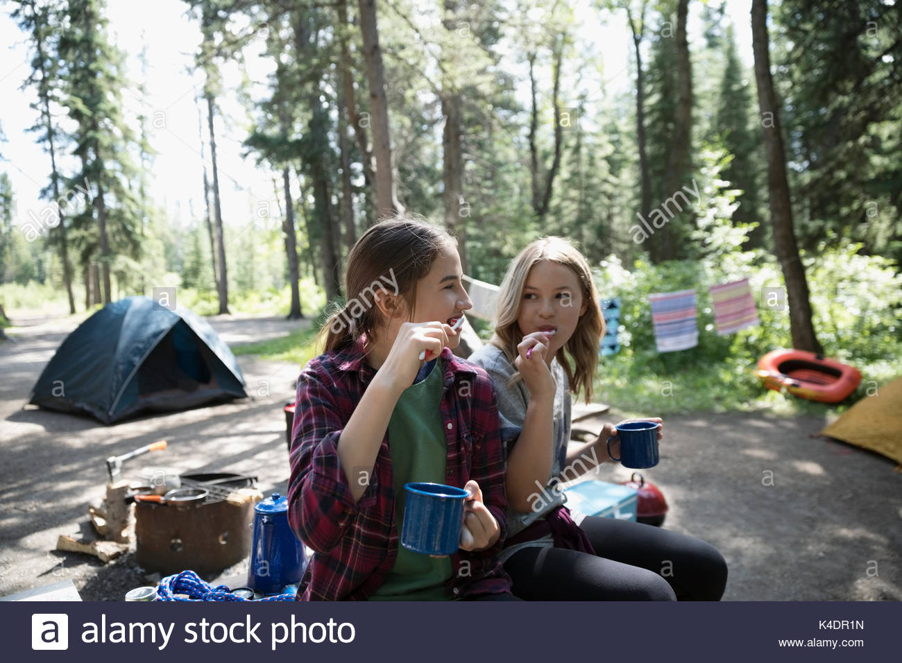 Teenage girl friends brushing teeth with toothbrushes and mugs at outdoor school campsite - Stock Image