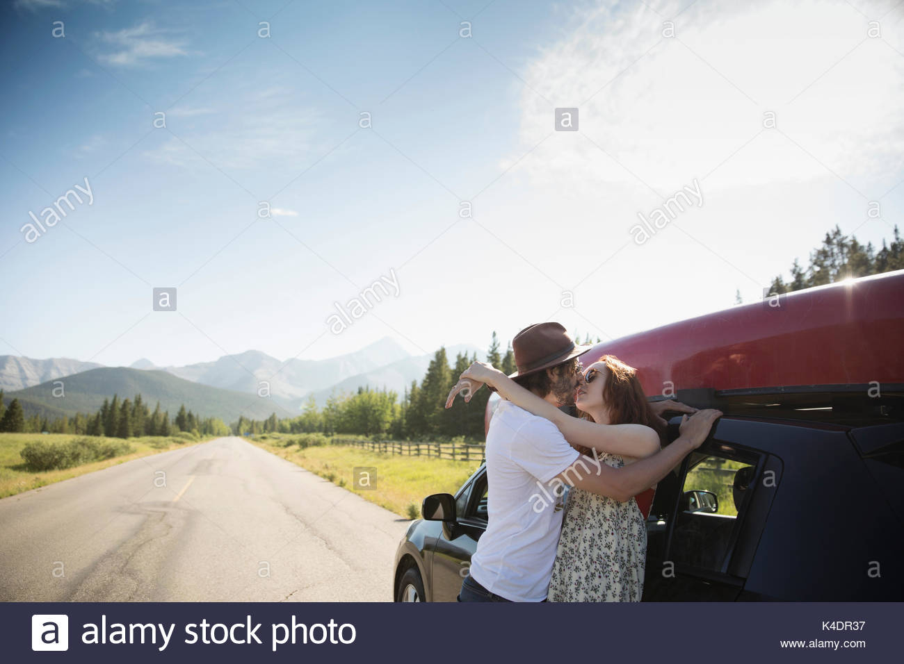 Affectionate young couple kissing outside car with canoe at sunny summer rural roadside - Stock Image