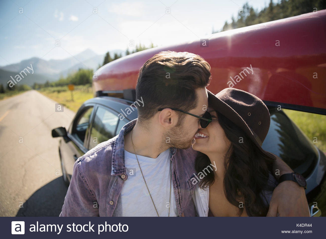 Affectionate young couple kissing outside car with canoe, enjoying road trip - Stock Image