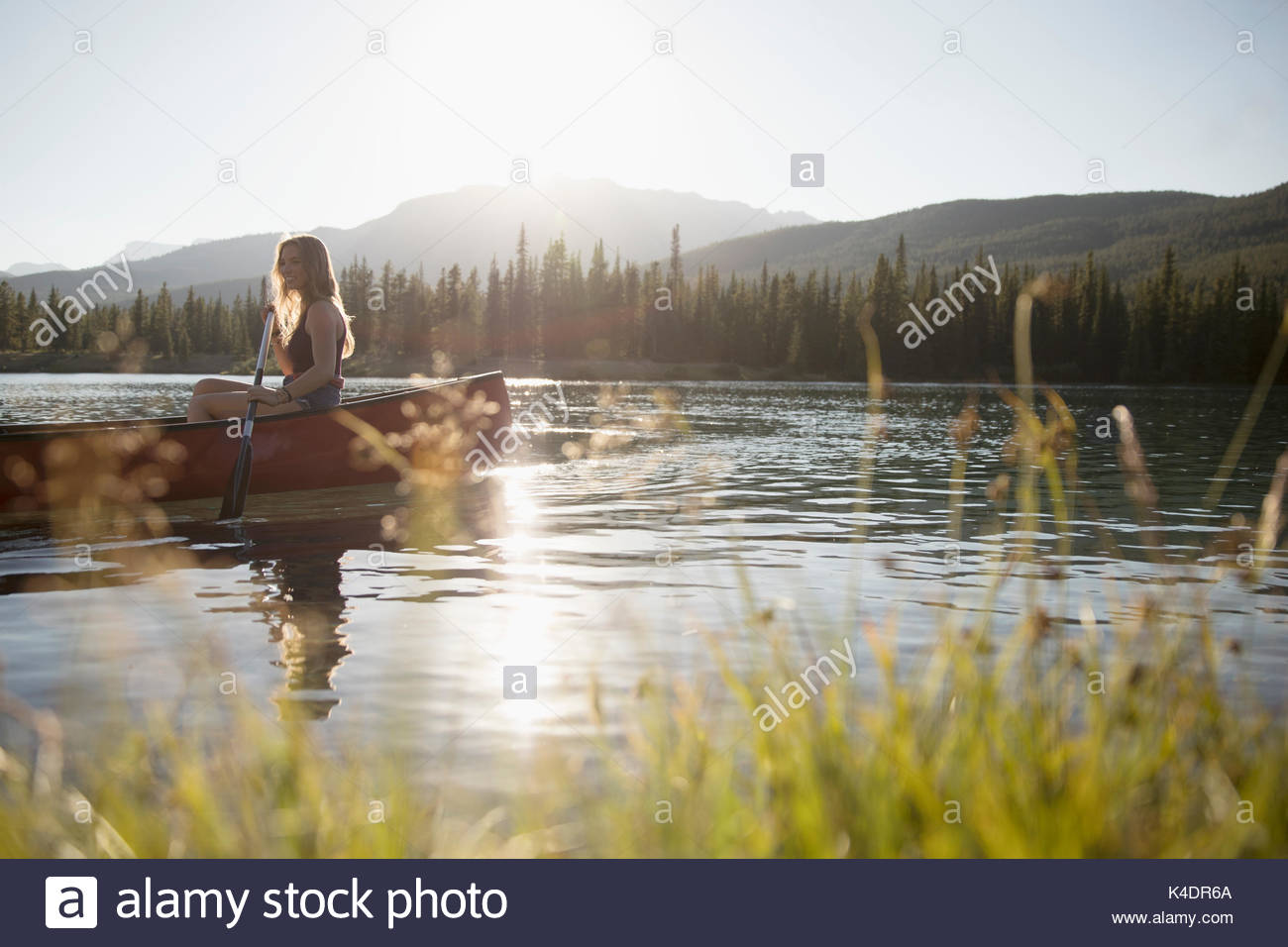 Woman paddling canoe with oar on tranquil sunny summer lake - Stock Image