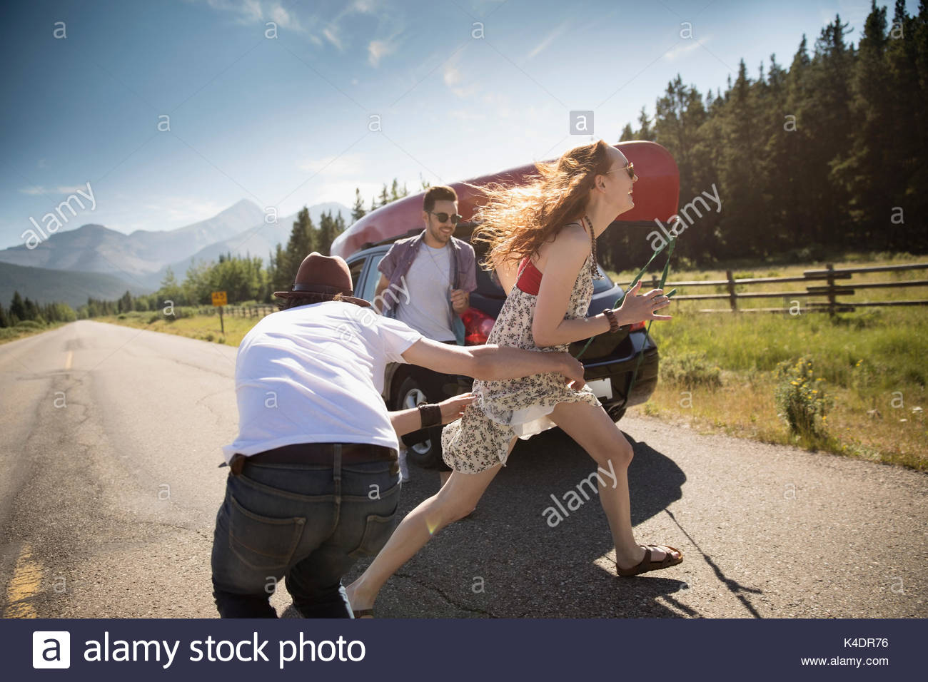 Playful friends on sunny rural road, enjoying summer road trip - Stock Image