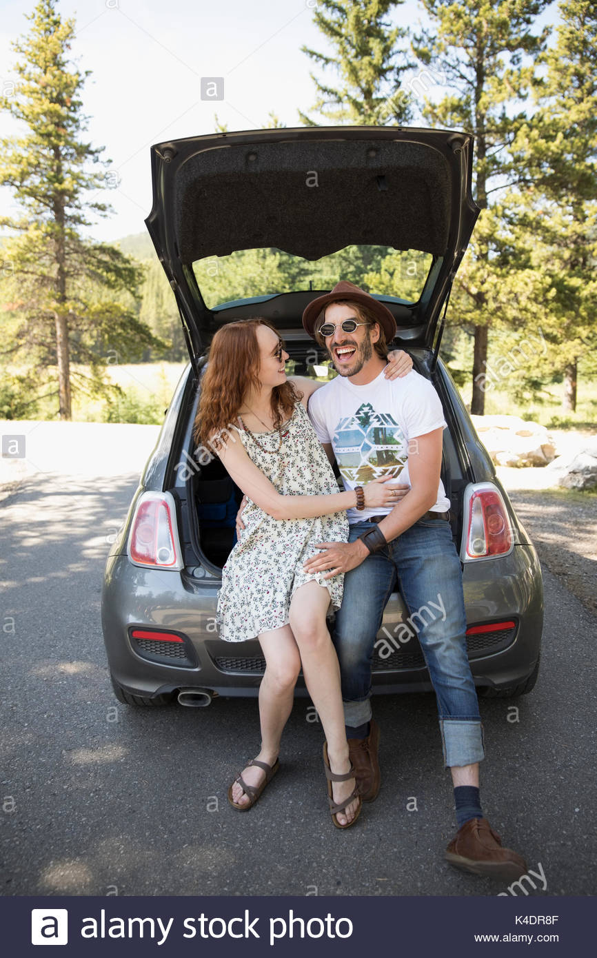 Laughing couple hugging in hatchback of car - Stock Image